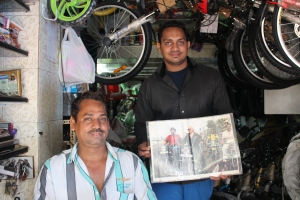 "Mr ""Happy Cycle Shop"" and son holding aloft a picture of them with Gregory David 'Shantaram' Roberts"